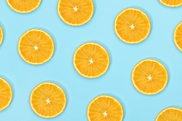 Fruchtmuster der frischen reifen scheibe orange auf blauem hintergrund. draufsicht