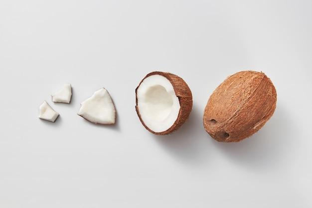 Fruchtmuster von verschiedenen teilen der frischen reifen natürlichen natürlichen organischen exotischen kokosnussfrucht auf einem hellgrauen hintergrund mit kopienraum. vegetarisches konzept.