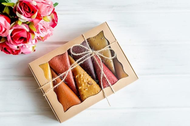 Fruchtpastille fruchtlederkegel in einer geschenkbox mit rosenstrauß