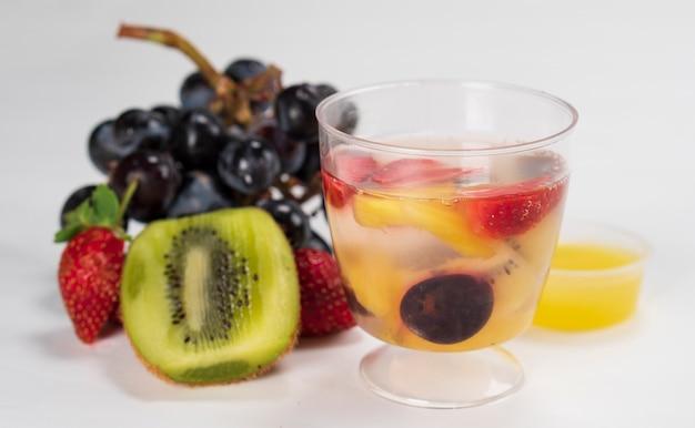 Fruchtpudding serviert mit frischem obst auf weißem hintergrund