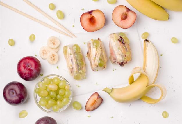 Fruchtrollen neben zutaten, banane, pflaume, apfel, traube auf weiß.