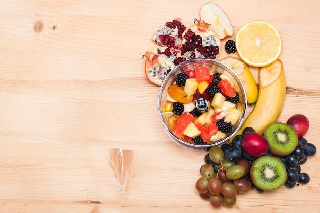 Fruchtsalat mit früchten auf hölzernem strukturiertem hintergrund