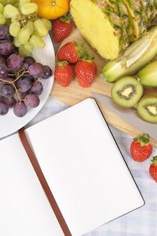 Fruchtsalat mit leerem rezeptbuch