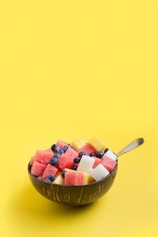Fruchtsalat von melone, wassermelone, blaubeere in kokosnussschale auf gelb.