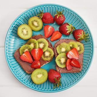 Fruchtsandwich, erdbeeren und kiwi. erdnussbutter toast.