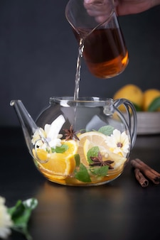 Fruchtzitrustee und glasteekanne auf schwarzem hintergrund. gesunder tee aus calendula