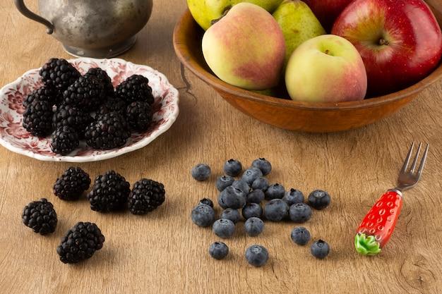 Früchte auf einer schüssel und beeren auf einem teller auf einem hölzernen brett über einem holztisch.