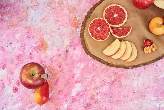 Früchte auf holzbrett auf rosa.