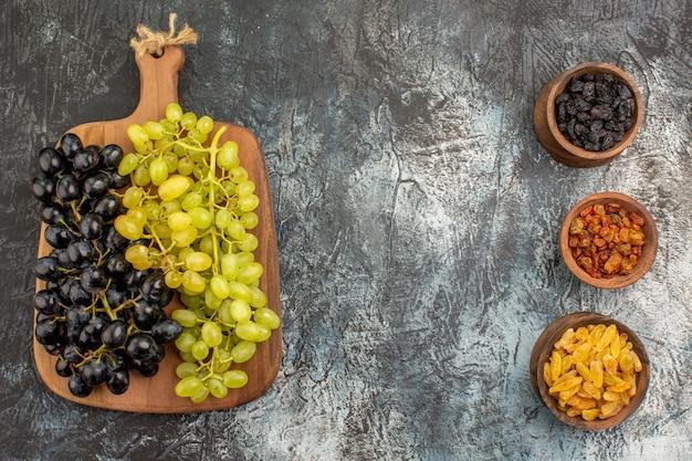 Früchte drei schalen mit getrockneten früchten grüne und schwarze trauben auf dem schneidebrett