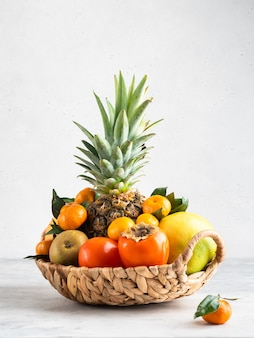 Früchte im korb isoliert. frische ananas, mandarinen, grapefruit, süßigkeiten, birnen und kaki-früchte. weißer hintergrund.