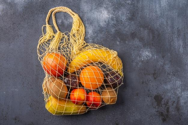 Früchte im sortiment in gelber öko-saitentasche auf dunkler holzoberfläche