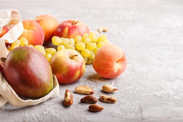 Früchte in der wiederverwendbaren baumwolltextilweißen tasche auf einem grauen konkreten hintergrund null überschüssiges einkaufsspeicher- und -wiederverwertungskonzept