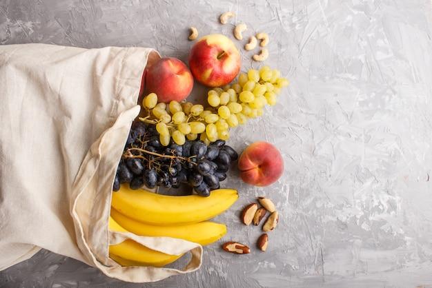 Früchte in der wiederverwendbaren baumwolltextilweißen tasche auf einer grauen konkreten einkaufsspeicher- und -wiederverwertungskonzeptebenenlage des hintergrundes null