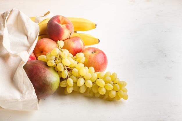Früchte in der wiederverwendbaren baumwolltextilweißen tasche auf weißem hölzernem hintergrund null überschüssiges einkaufsspeicher- und -wiederverwertungskonzept