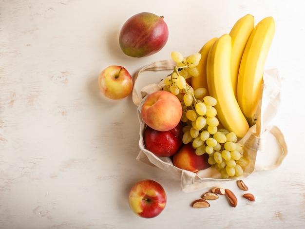 Früchte in der wiederverwendbaren baumwolltextilweißen tasche auf weißem hölzernem hintergrund. zero waste shopping, lagerung und recycling-konzept. draufsicht, kopie, raum.