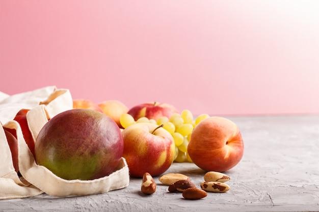 Früchte in der wiederverwendbaren baumwolltextilweißtasche auf einem grauen und rosa hintergrund. zero waste shopping, lagerung und recycling-konzept. seitenansicht, abschluss oben, kopienraum.