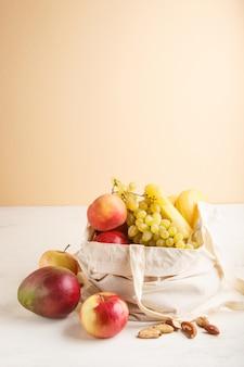 Früchte in der wiederverwendbaren baumwolltextilweißtasche auf weißem hölzernem. zero waste shopping, lagerung und recycling. seitenansicht, exemplar.