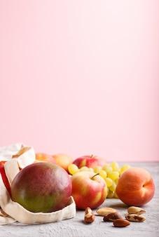 Früchte in der wiederverwendbaren weißen baumwolltextiltasche auf einem grau und einem rosa. zero waste shopping, lagerung und recycling. seitenansicht, abschluss oben, copyspace.