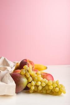 Früchte in der wiederverwendbaren weißen baumwolltextiltasche auf weiß und rosa. zero waste shopping, lagerung und recycling. seitenansicht, exemplar.
