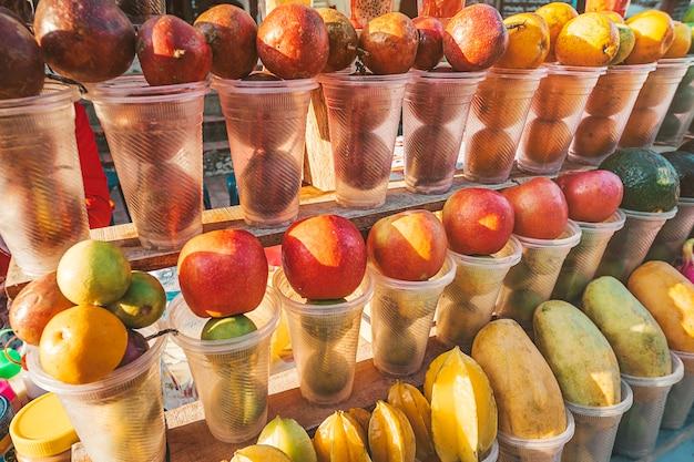 Früchte in plastikbechern, die auf dem markt in luang prabang zu frischen fruchtshakes verarbeitet werden können, verschiedene reife früchte auf der theke in asien.