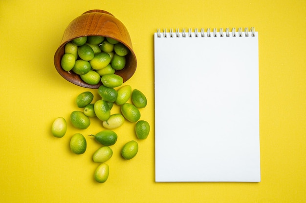 Früchte in schüssel obstschale neben dem weißen notizbuch und grünen früchten