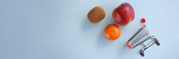 Früchte mit einem einkaufswagen aus dem supermarkt liegen auf blauem hintergrund