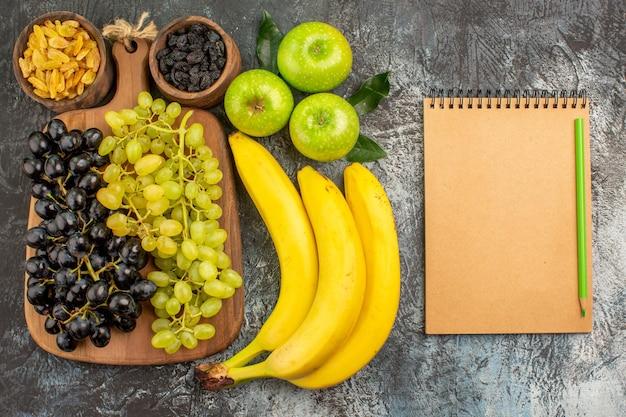 Früchte trauben trockenfrüchte bananen drei äpfel sahne notizbuch und grüner bleistift