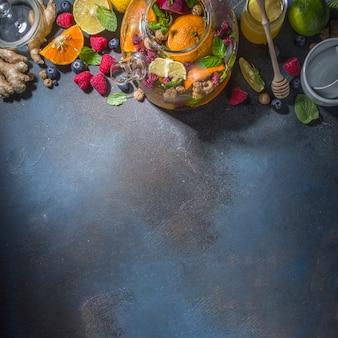 Früchte- und beerentee in der teekanne. heißgetränk mit zitrone, minze, blaubeere, ingwer, orange, apfel. heißes aromatisiertes dampfgetränk auf dunkelblauem hintergrundkopierraum