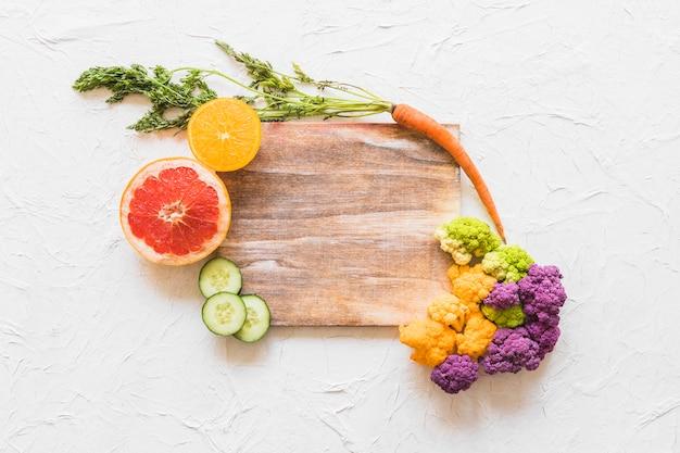 Früchte und blumenkohl auf holzklotz über weißem beschaffenheitshintergrund