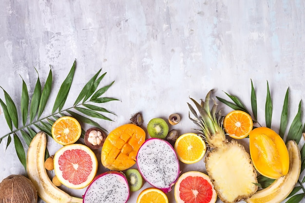 Früchte und palmblätter auf weißer oberfläche