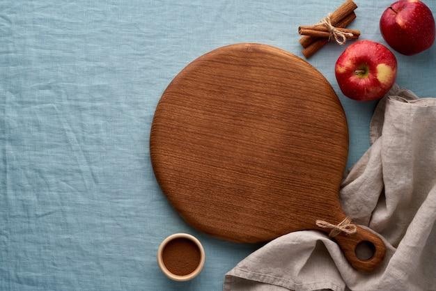 Früchte und rundes holzschneidebrett auf blauer leinentischdecke
