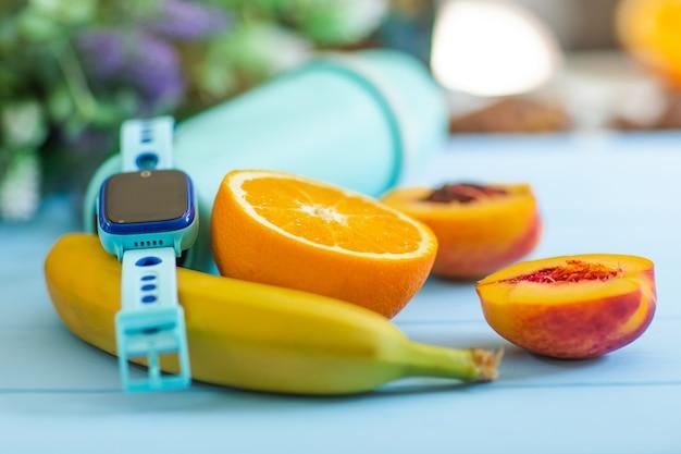Früchte und smartwatch auf blauem holzschreibtisch