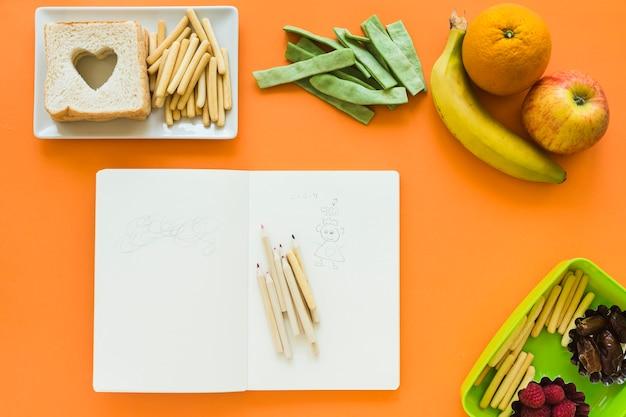 Früchte und snacks um notizblock