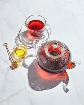 Früchtetee mit äpfeln und thymian und honig in glasteekanne und tasse auf weißem hintergrund mit harten schatten shadow
