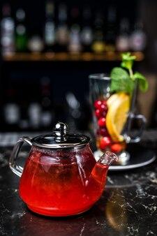 Früchtetee mit preiselbeeren, teekanne und glas