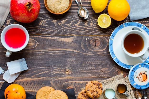Früchtetee mit zitrone, milch, honig, orange, granatapfel, auf einem hölzernen hintergrund