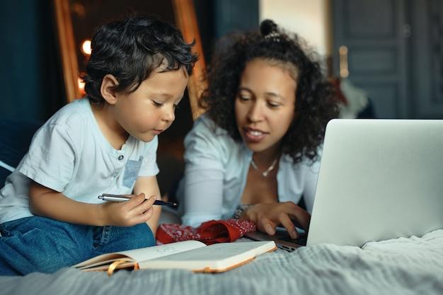 Frühe entwicklung, bildung, kindheit und moderne elektronische geräte. porträt der fürsorglichen jungen lateinischen frau auf dem bett unter verwendung des laptops