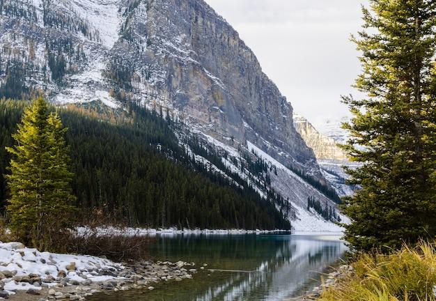 Frühe winteransicht des fairview mountain mit reflexion über lake louise im banff national park, alberta, kanada