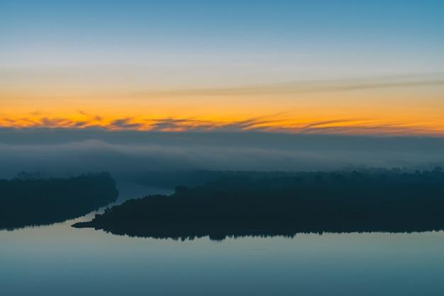 Früher blauer himmel reflektiert im flusswasser. flussufer mit wald unter himmel vor dem morgengrauen. gelber streifen im malerischen himmel. nebel versteckte bäume auf der insel. atmosphärische landschaft des mystischen morgens der majestätischen natur.