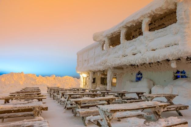 Früher morgen. leeres café auf dem gipfel eines berges in einem skigebiet. viel schnee