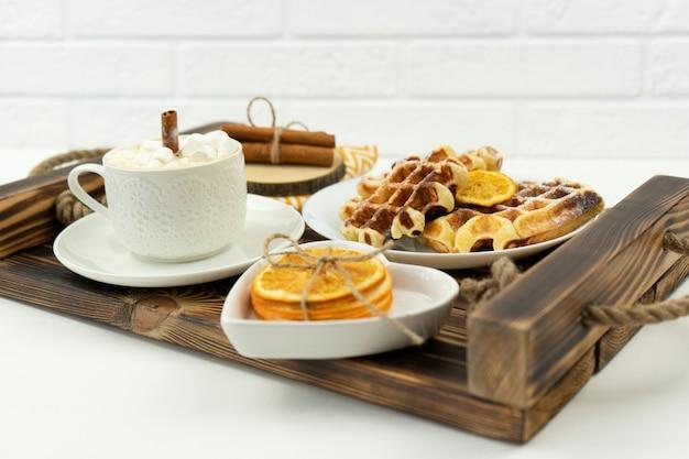 Frühes frühstückskaffee mit marshmallows und einer zimtstange und belgischen waffeln liegt auf einem holztablett
