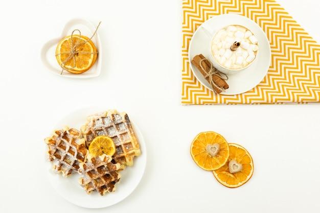 Frühes frühstückskaffee mit marshmallows und einer zimtstange und belgischen waffeln