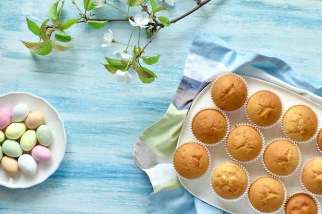 Frühjahr- oder ostern-ebenenlage mit platte von zitronenmuffins und von marzipaneiern auf hellblauem hintergrund mit apfelblumen