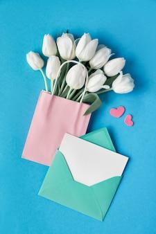 Frühjahrebenenlage, weiße tulpen in der papiertüte auf hintergrund der blauen minze mit umschlag, leerer karte und dekorativen herzen