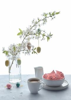 Frühjahrkaffee und -bonbons auf einem holztisch mit dem baumzweig bedeckt mit blüten