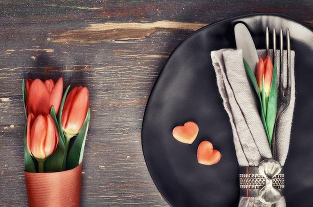 Frühjahrmenükonzept mit frischen tulpen und herzdekoration auf dunklem holz
