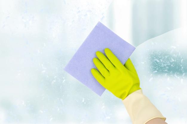 Frühjahrsputz-konzept. draufsicht der hand in gelben gummihandschuhen, die das fenster mit einem weichen lappen reinigen. das konzept des reinigungsdienstes.