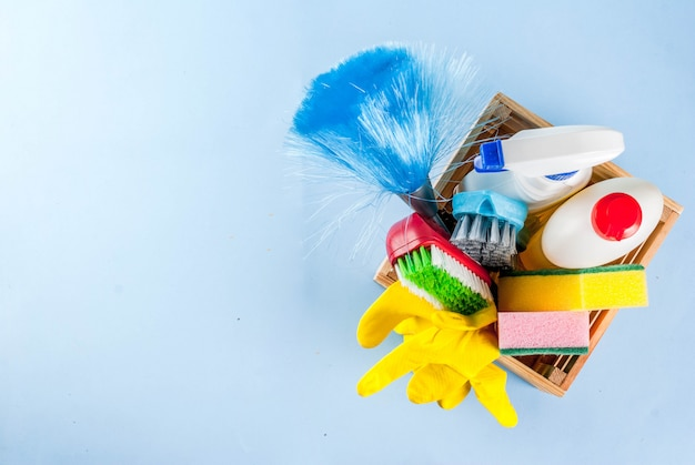 Frühjahrsputzkonzept mit versorgungen, hausreinigungsproduktstapel. hausarbeitkonzept, auf draufsicht des hellblauen hintergrundkopienraumes
