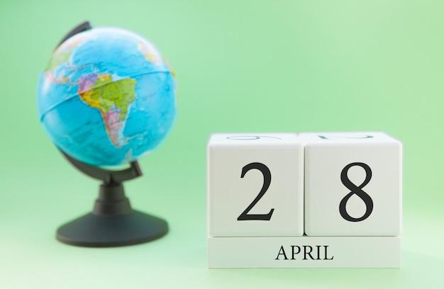 Frühling 28. april kalender. teil eines sets auf unscharfem grünem hintergrund und kugel.
