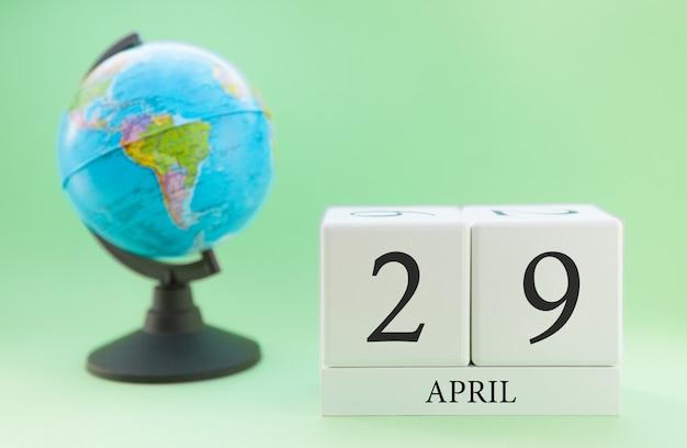 Frühling 29. april kalender. teil eines sets auf unscharfem grünem hintergrund und kugel.